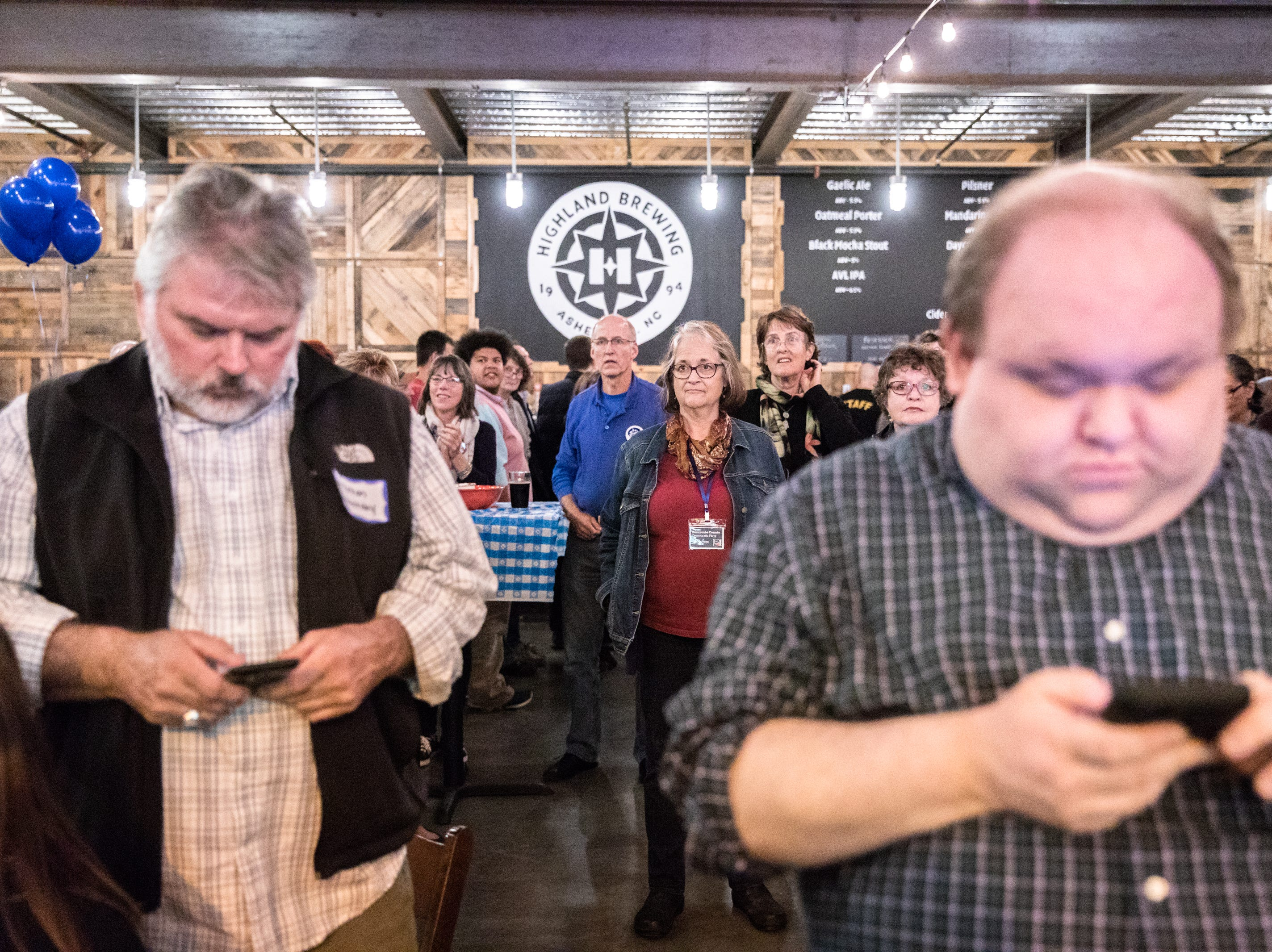 People gathered at Highland Brewing for the Democratic Party election night party in support of local and national candidates, watching as results are announced, Nov. 6, 2018.