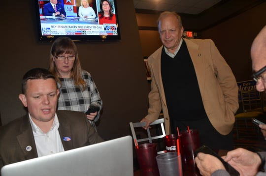 Dr. John Bizon (right) monitors election results with Keith den Hollander and Jeannie Burchfield.