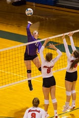 Fowlerville's Jackie Jarvis goes high for a hit against Marshall in this Division 2 regional semifinal