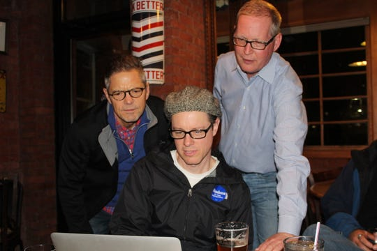 Democrat Jim Haadsma, at right, watches election results for the 62nd District state representative race with former Congressman Mark Schauer, at left, and Campaign Manager Andy  Helmboldt.