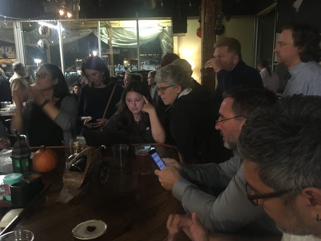 South Kitsap School Supporters check election results on Tuesday night at Slaughter County Brewery in Port Orchard.
