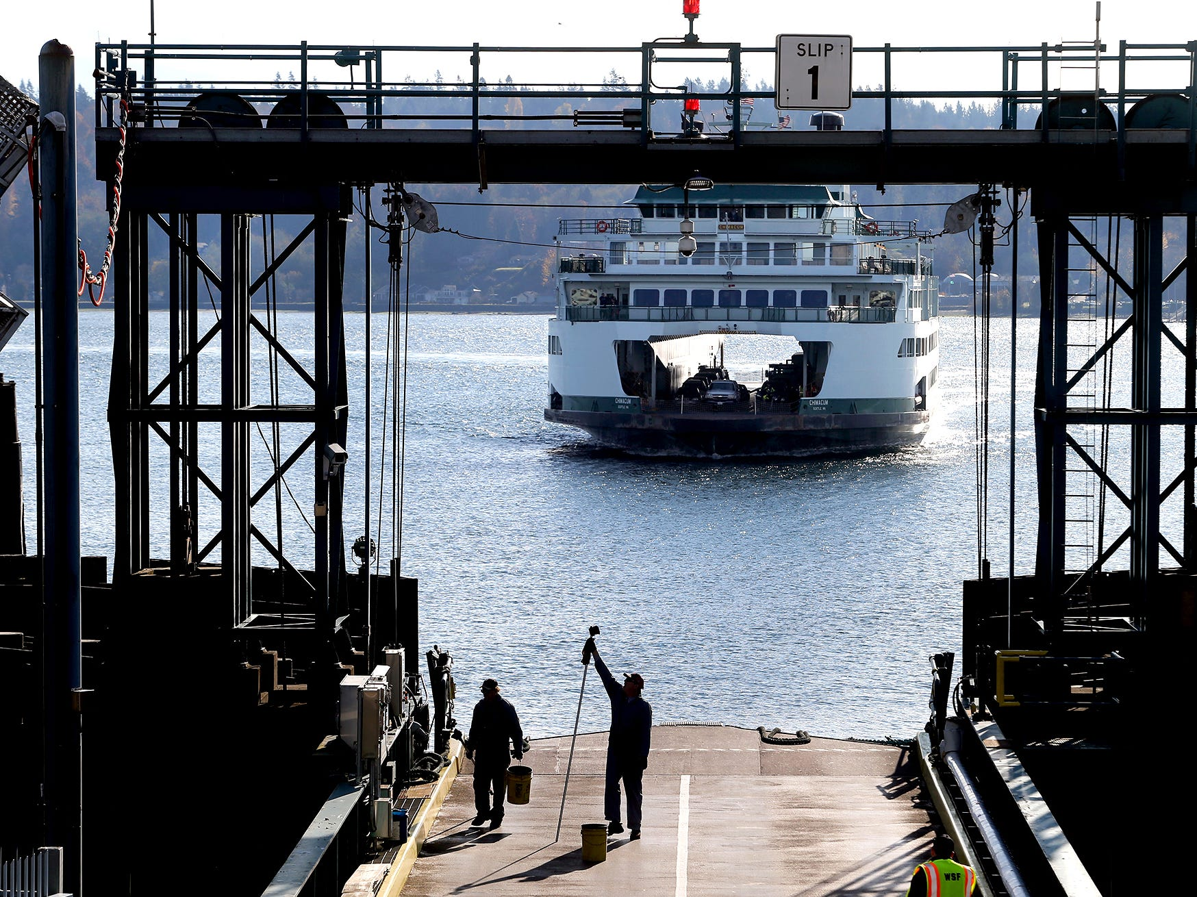Workers finish on slip number 1 at the Bremerton Ferry Terminal on Wednesday, November 7, 2018, as the Chimacum approaches.