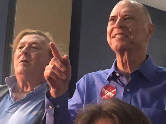 Rep. Bill Posey, District 8, right, views election results with supporters at a watch party at Holiday Inn in Viera.