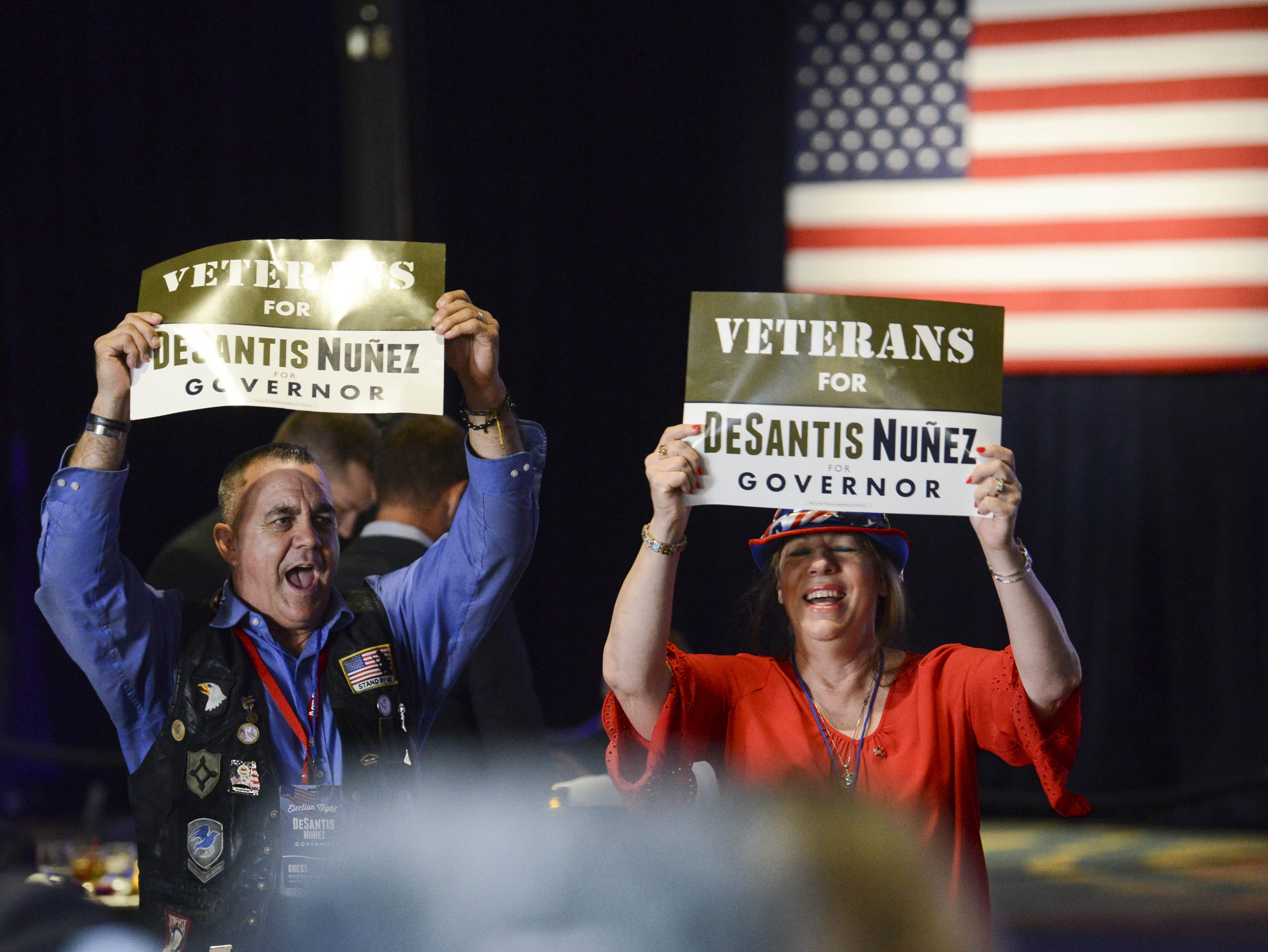 Ron DeSantis supporters wave signs during DeSantis' election watch party in Orlando. Early results give him a slight edge in the Florida gubernatorial race.