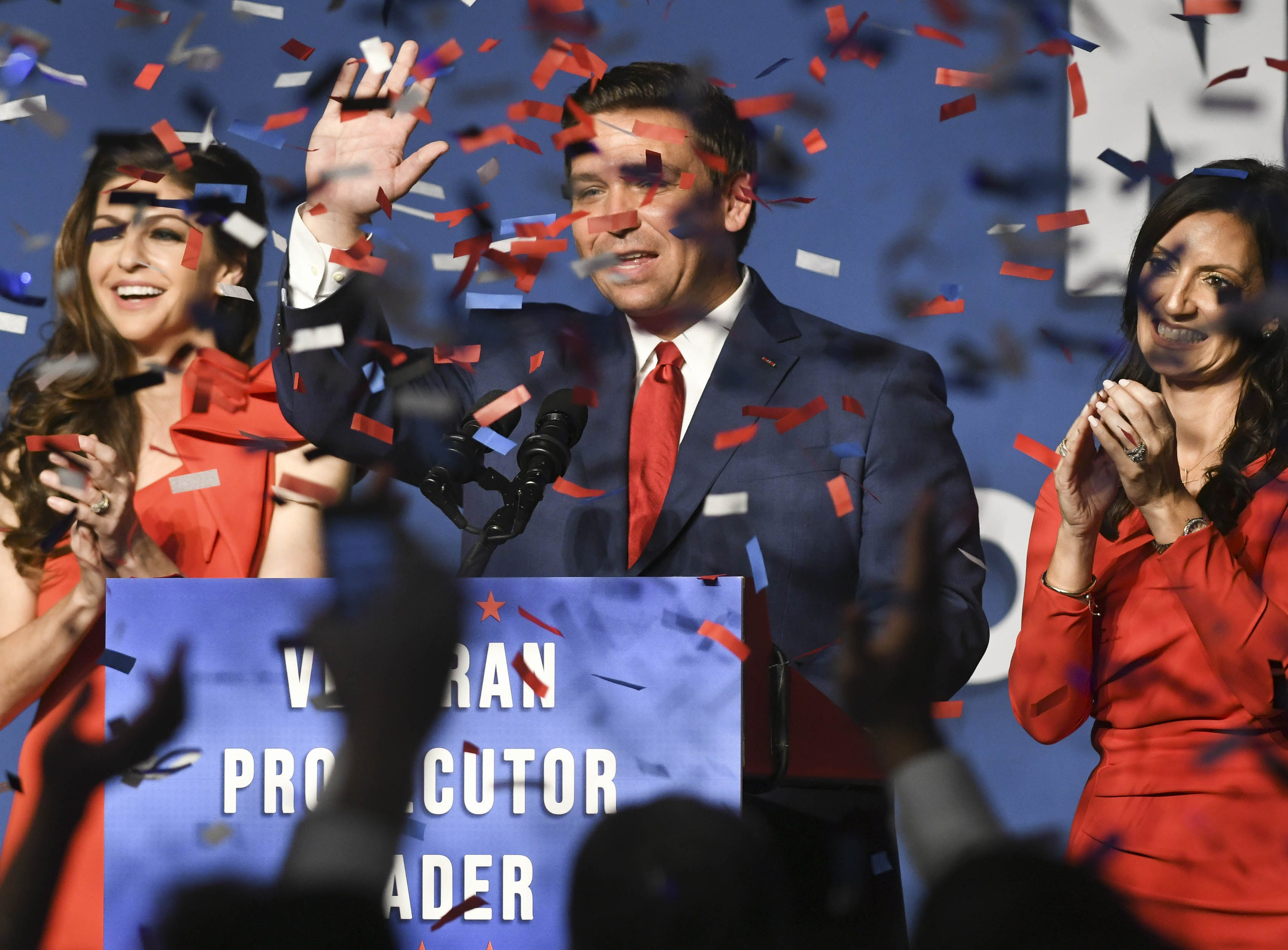 Ron DeSantis, his wife Casey (left) and Lt. Governor-elect Jeanette Nunez wave to supporters Tuesday in Orlando.
