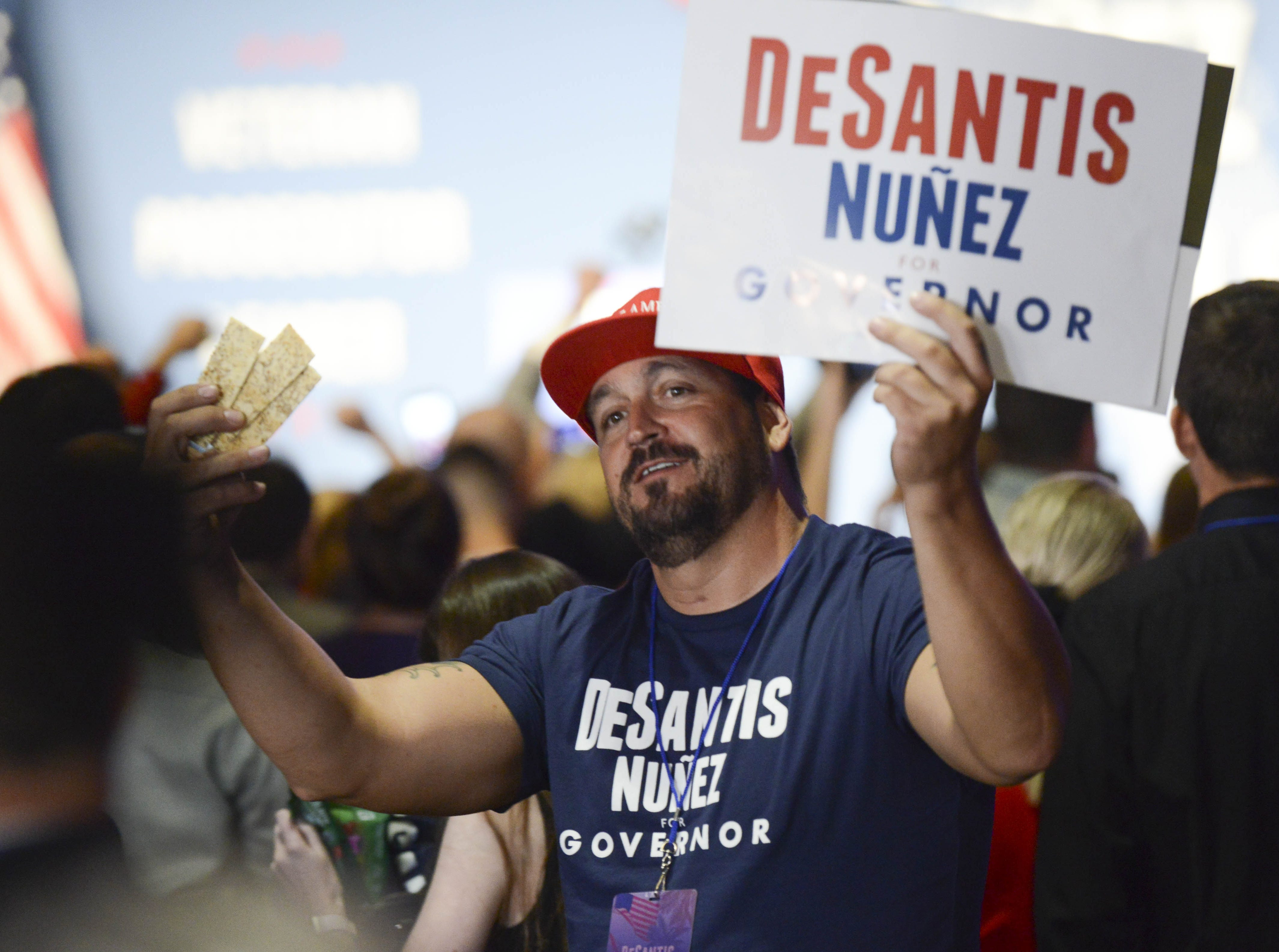 A supporter of Ron DeSantis waves a sign during the election watch party in Orlando.