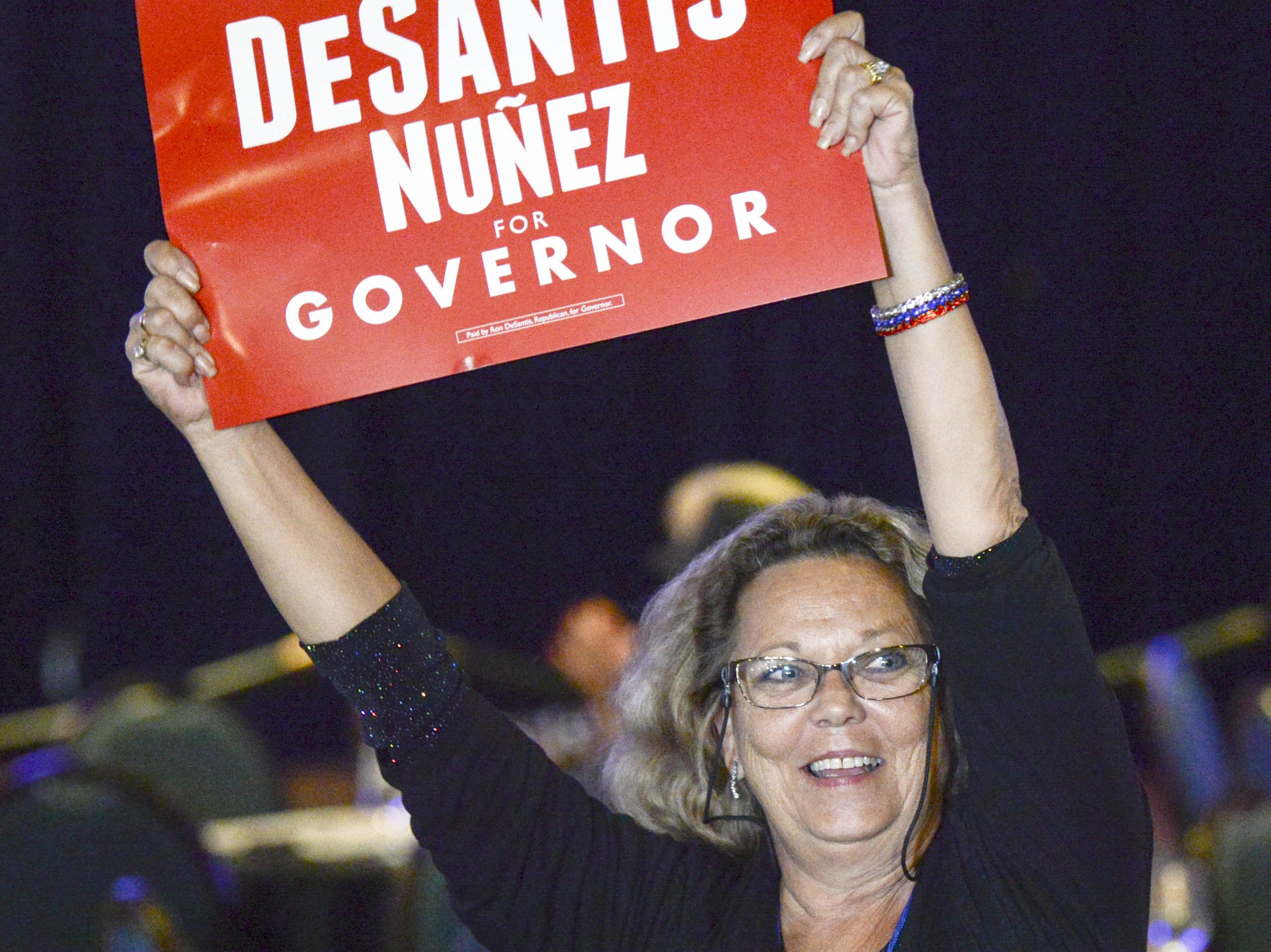 A Ron DeSantis supporter waves a sign during DeSantis' election watch party in Orlando.