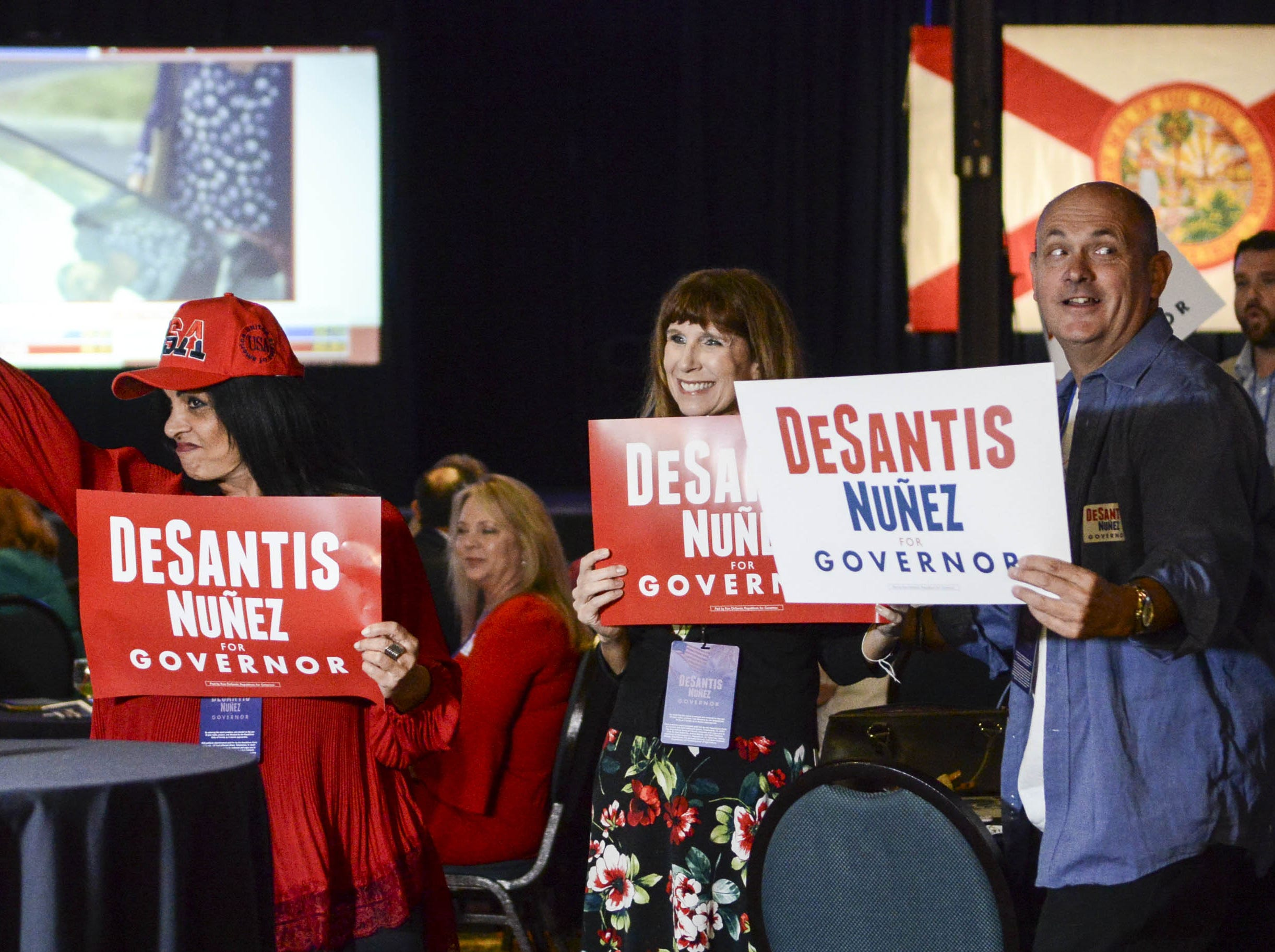 Ron DeSantis supporters wave signs during DeSantis' election watch party in Orlando.