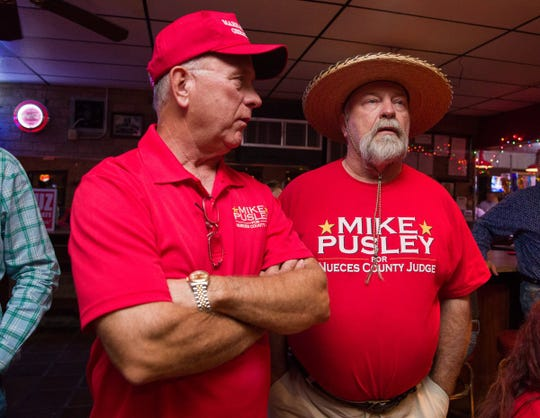 Republican candidate Mike Pusley talks with his brother, Lance Pusley, about early voting numbers in the Nueces County judge race on Tuesday, Nov. 6, 2018.