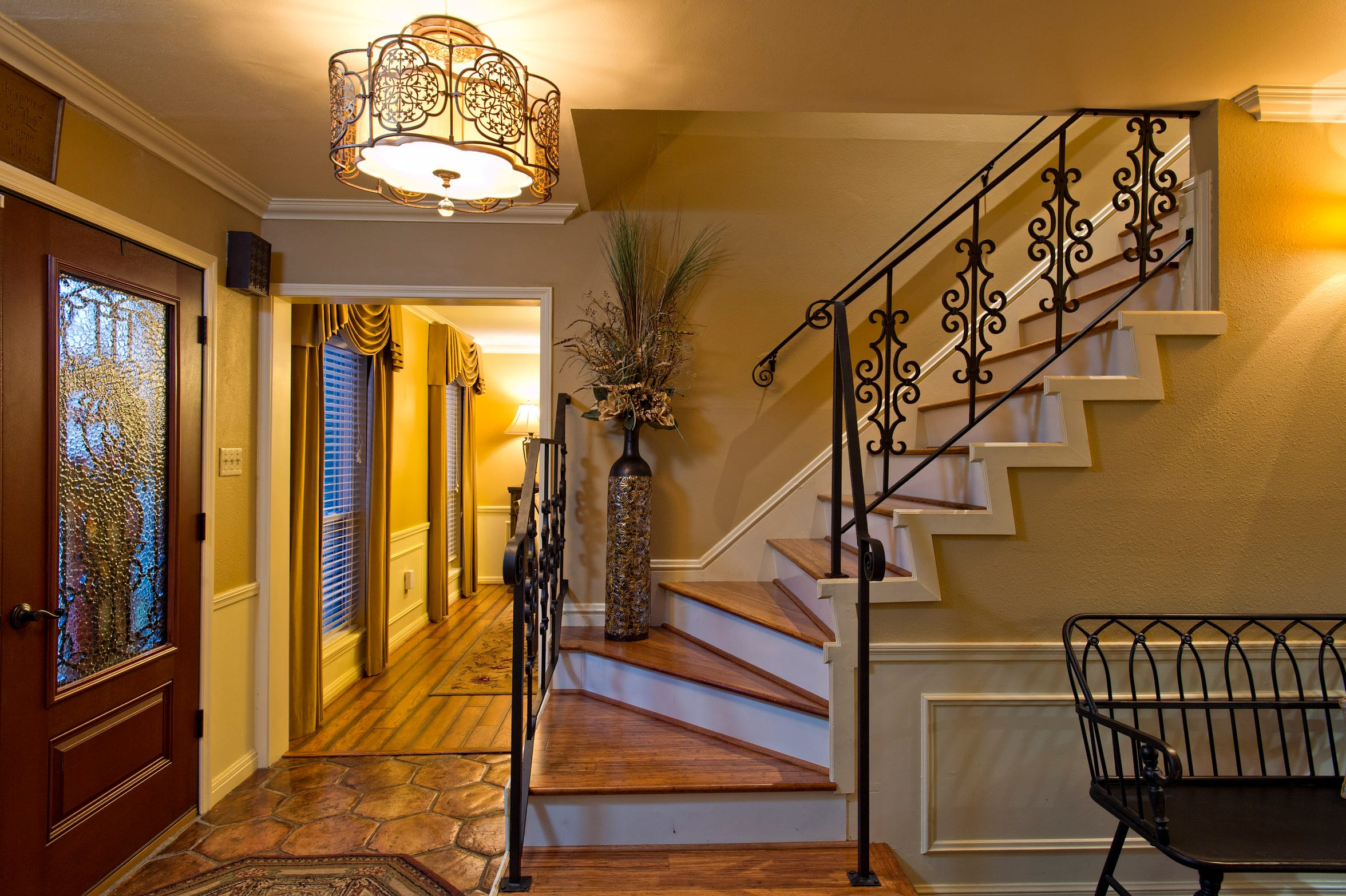 A striking wrought iron and wood stairway rises from the saltillo tiled  entry foyer