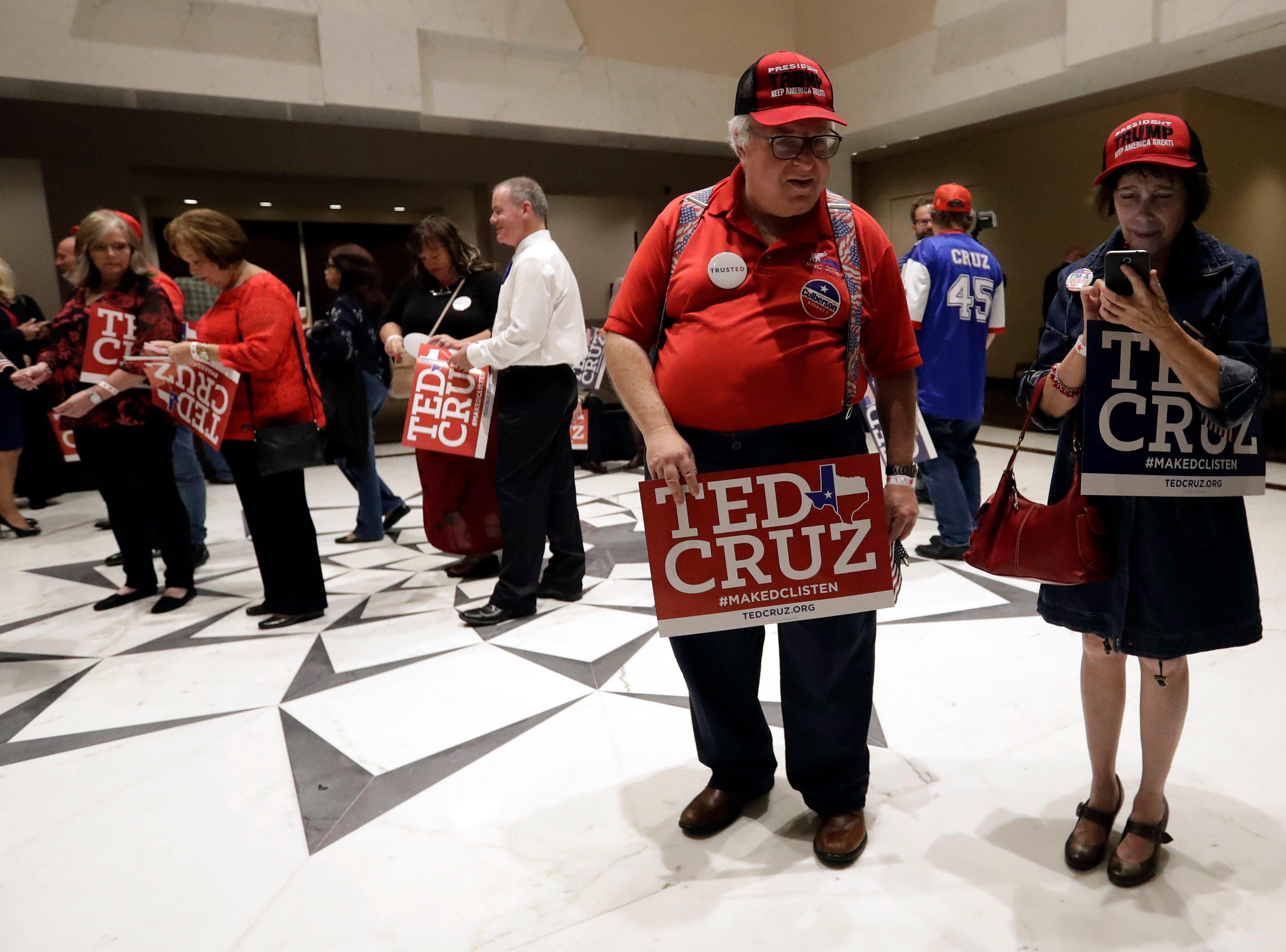 Stuart Mayper, left, and Elena Voltman, right, wait to enter an election night party for Sen. Ted Cruz, R-Texas, Tuesday, Nov. 6, 2018, in Houston. (AP Photo/David J. Phillip)