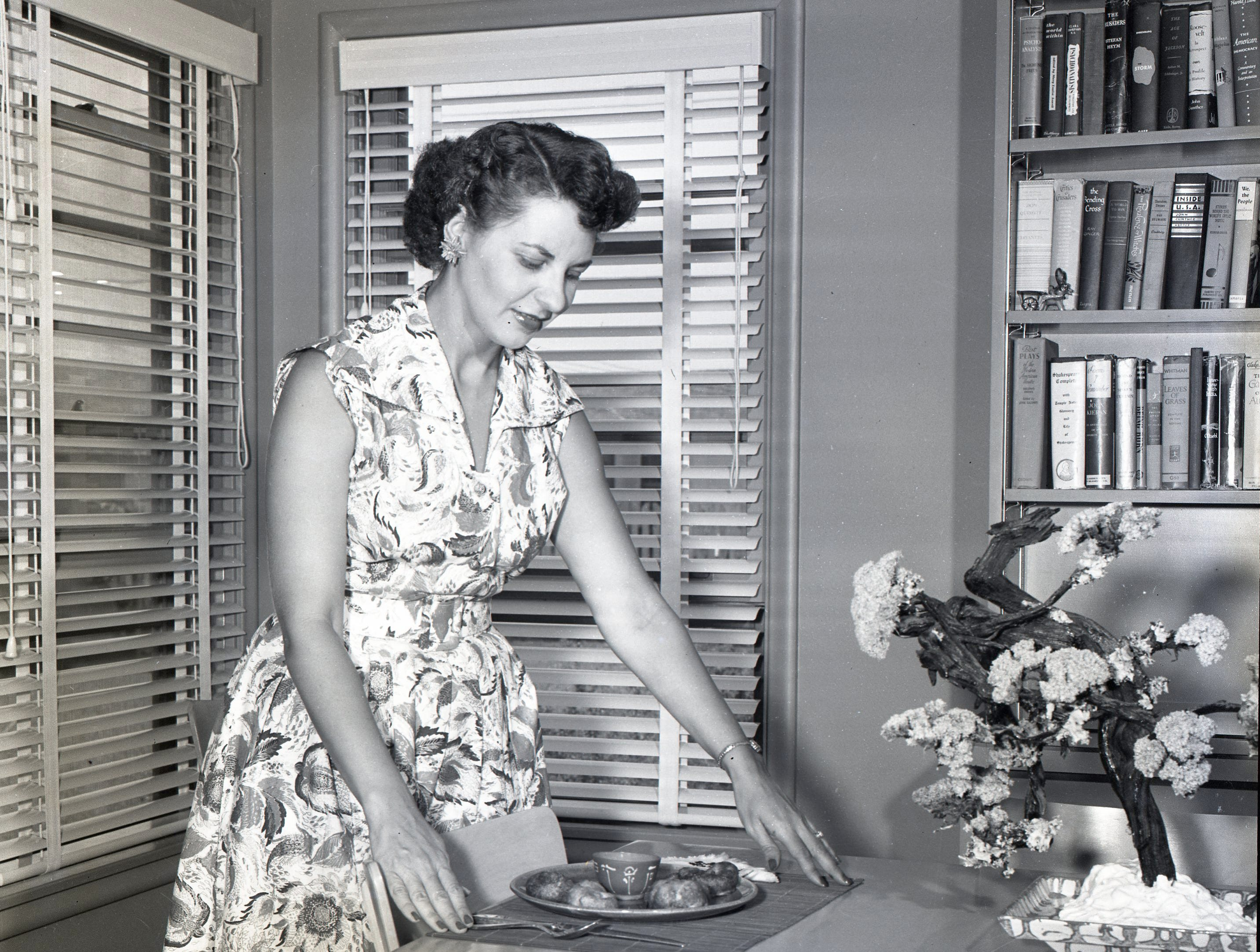 Mrs. Stanley C. Pearl places a dish of Chinese fried shrimp on the table at her home in June 1951. She contributed several Chinese recipes to the cookbook compiled by the Temple Beth El Sisterhood in 1951.