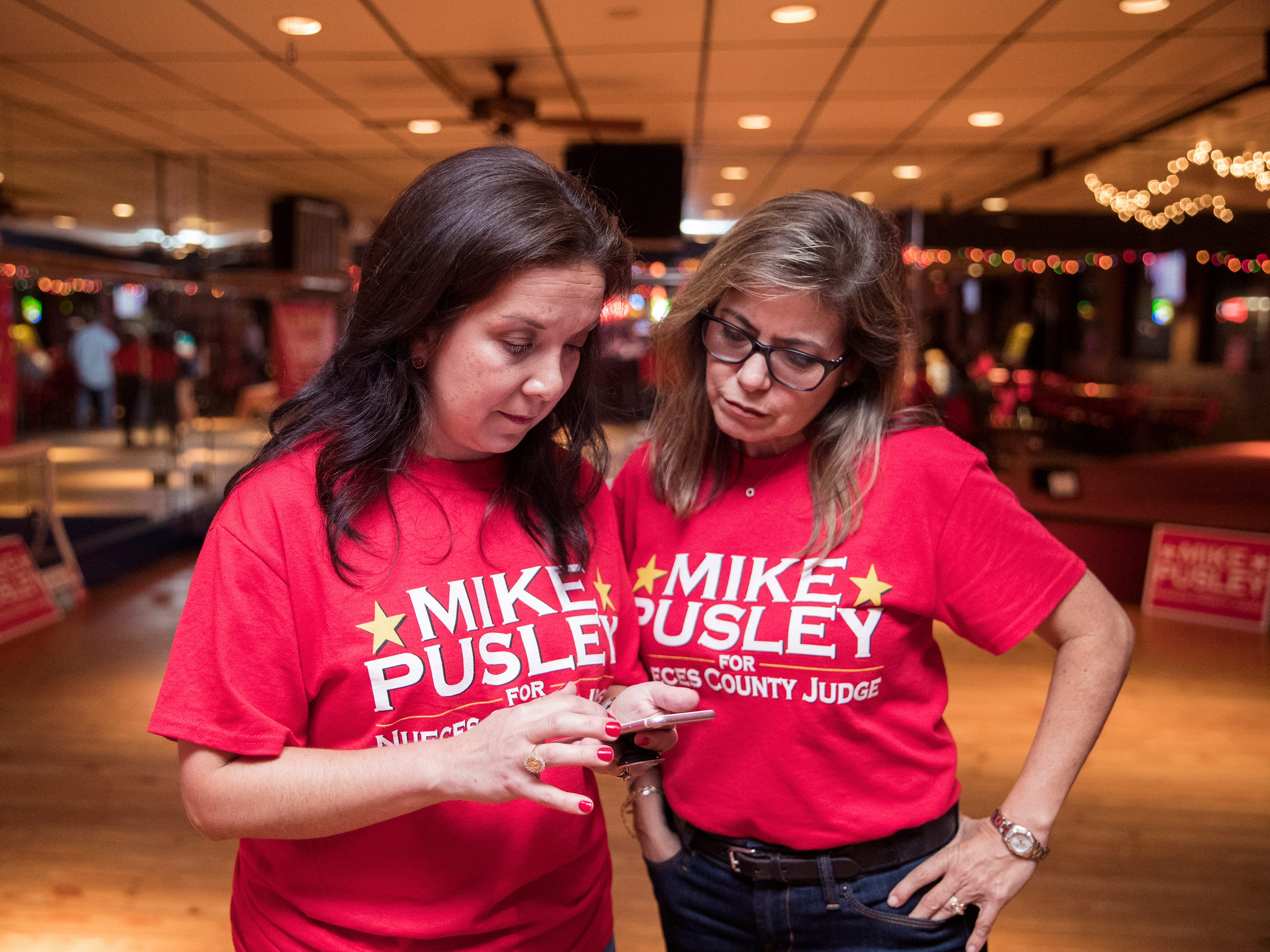 Members of the Mike Pusley campaign team, Jessica Davila-Burnett (left) and Pam OÕConnor, look at early voting numbers for the Nueces County Judge race at the Bar-B-Q Man on Tuesday, November 6, 2018.