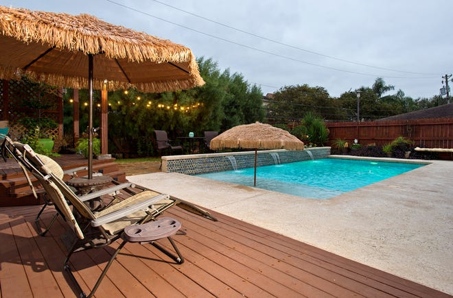 The backyard is an oasis complete with a pool, lush landscaping, pergola & several sitting areas.
