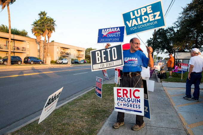 Akbar Abba is decked out in candidate signs outside the Deaf and Hard of Hearing Center on Tuesday, November 6, 2018.