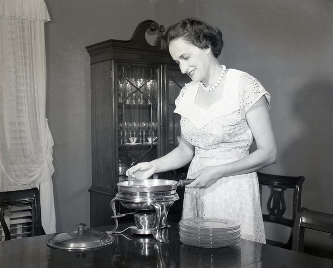 Mrs. Sidney Wolf stirs the batter for crêpes suzette in a chafing dish in June 1951. The recipe was included in a 1951 cookbook by the Temple Beth El Sisterhood.