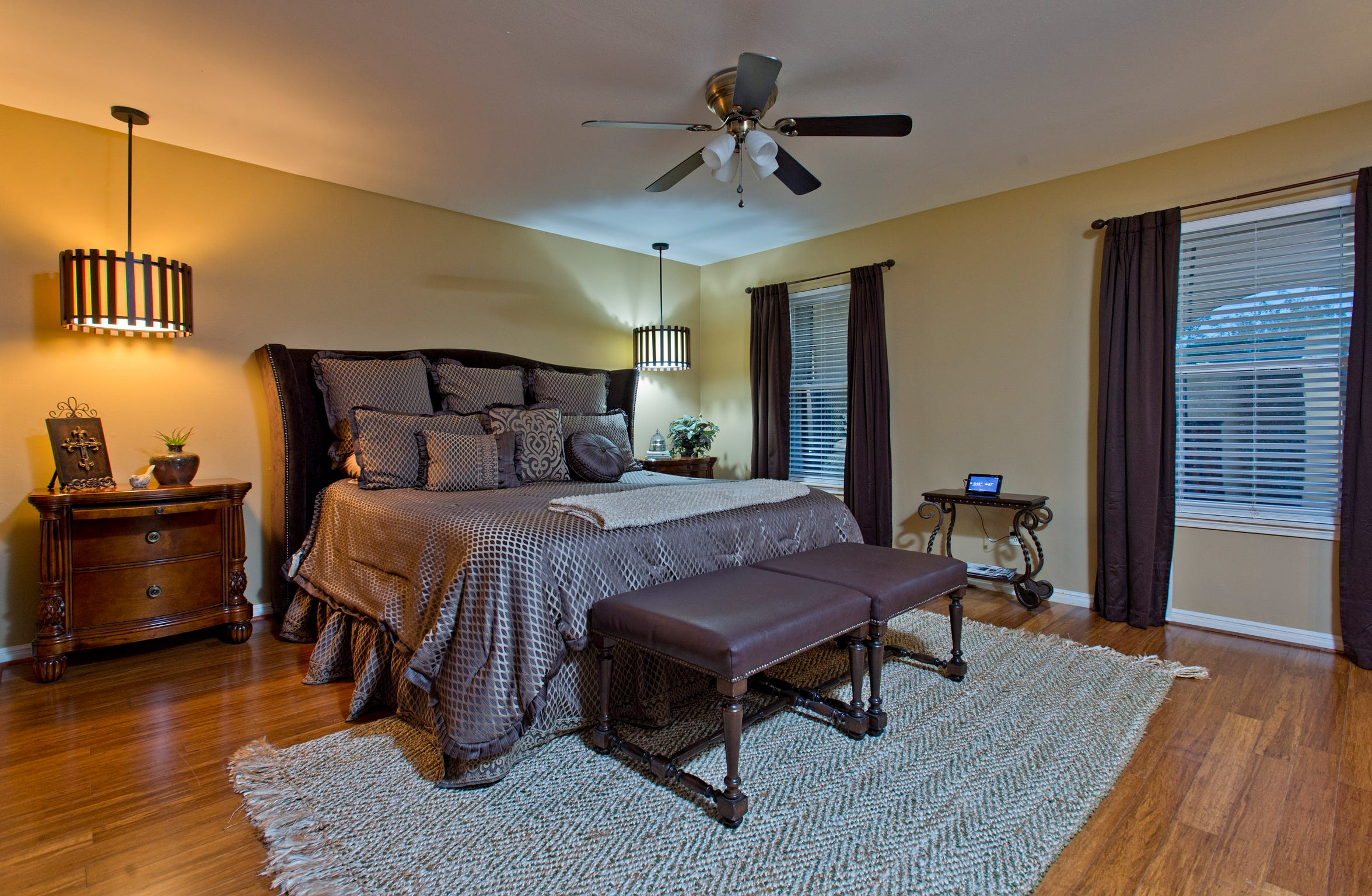 A spacious master bedroom features hardwood flooring, unique lighting and views of the grounds