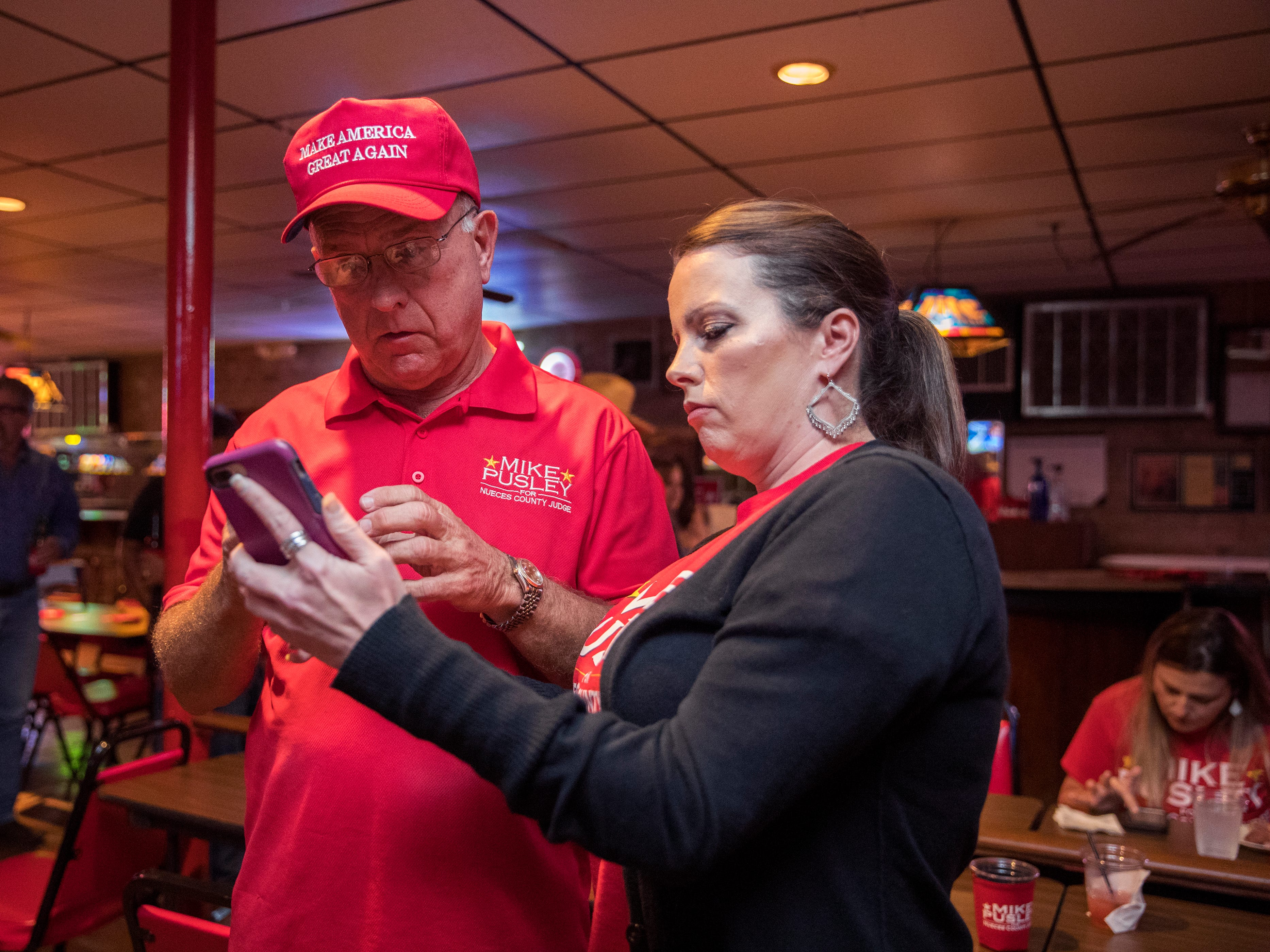 Republican candidate for Nueces County Judge Mike Pusley (left) looks at early voting numbers with his daughter Candi Pusley during his watch party at the Bar-B-Q Man on Tuesday, November 6, 2018.