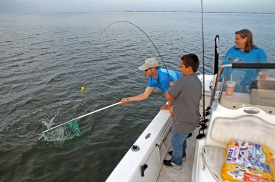 Capt. Jon Darnell nets a fish for Jacob as his mom watches.