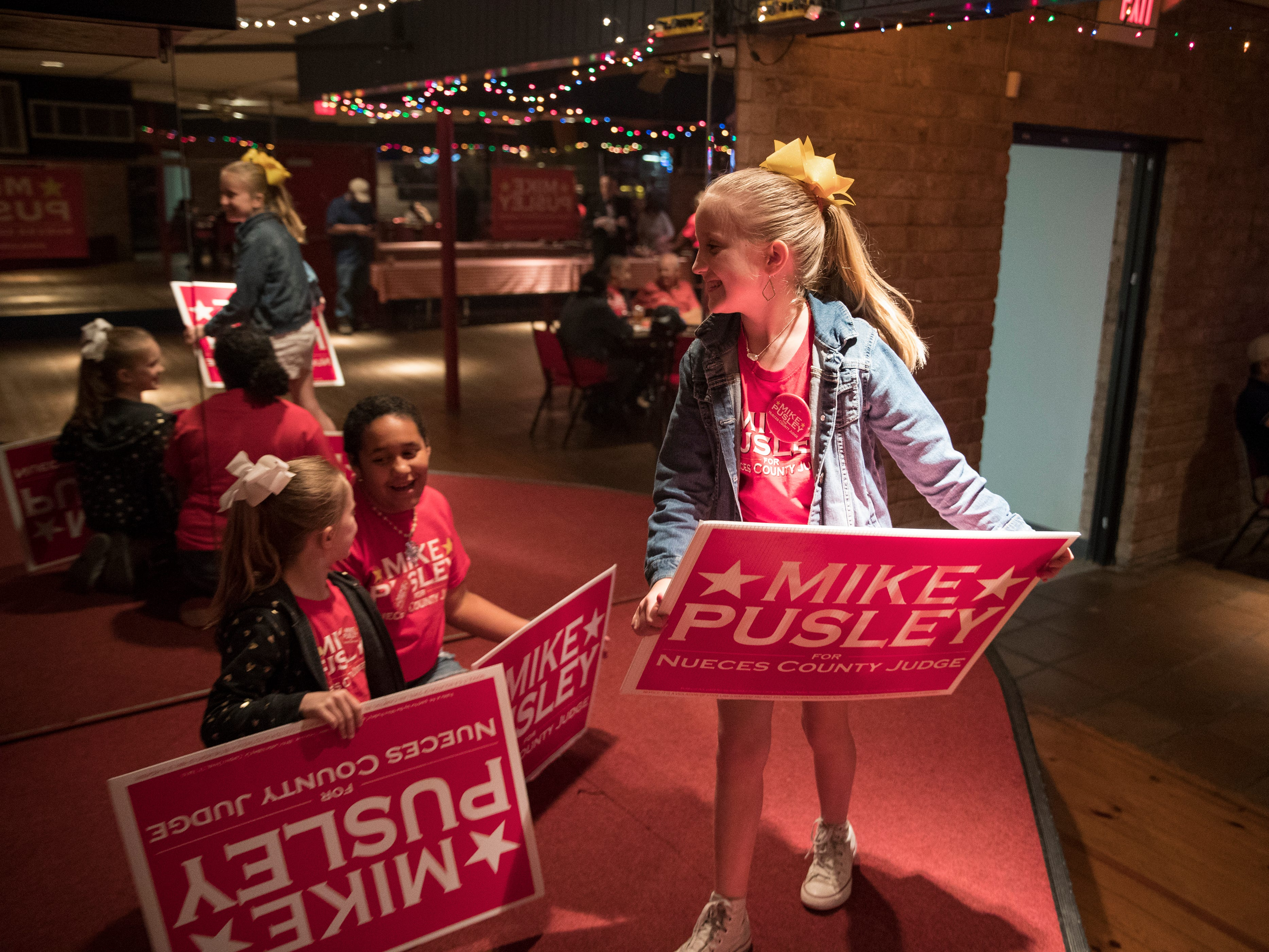 Kynleigh Tegeler (from left), 6, Kamryn Cleveland, 10, and Ryleigh Tegeler, 9, make up a cheer in support of Republican candidate for Nueces County Judge Mike Pusley at his watch party.