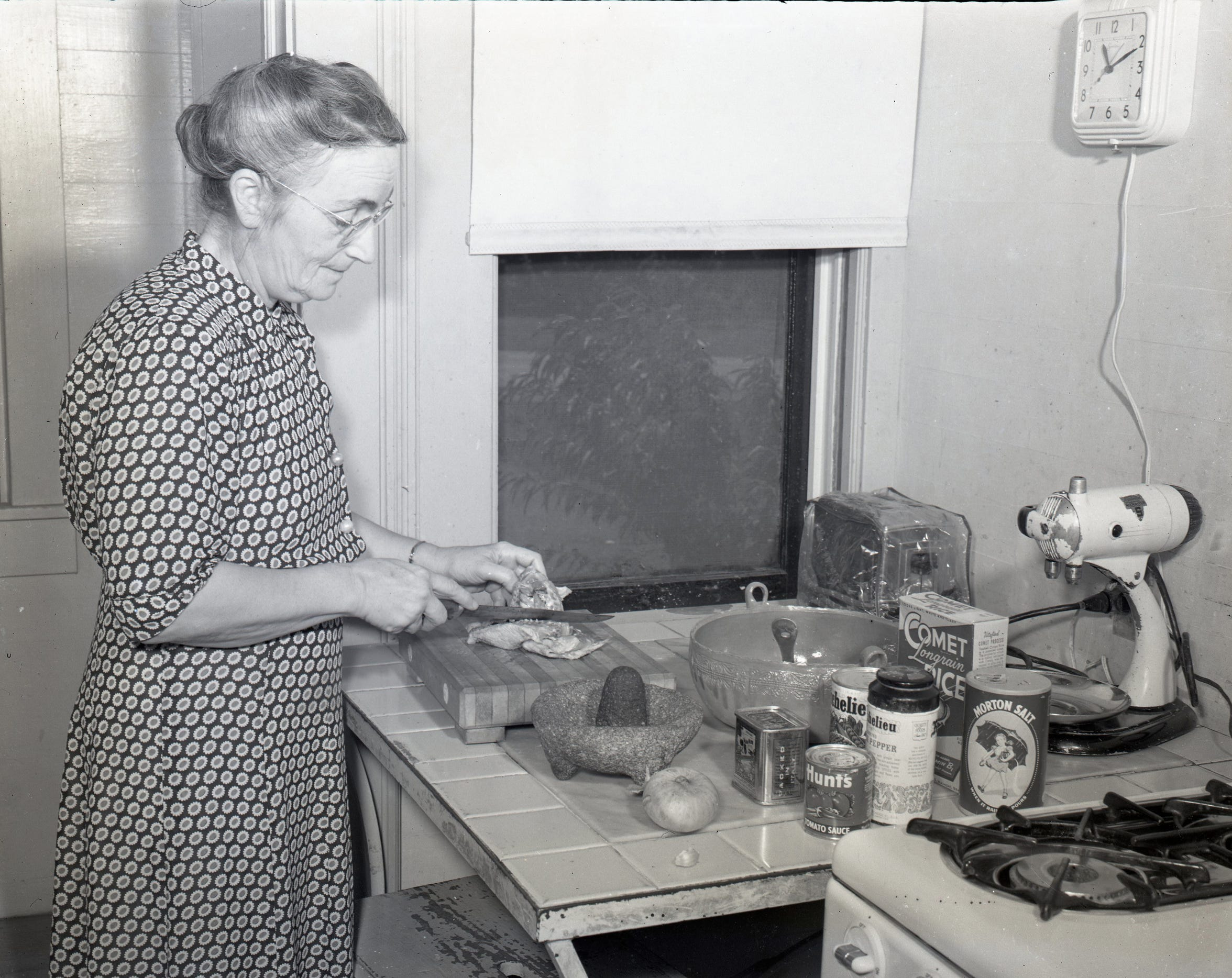 "Mrs. I.M. Alexander begins cooking preparations in her kitchen in June 1951. She contributed many of the recipes for Mexican dishes in the ""Cooking Gems"" cookbook by the Temple Beth El Sisterhood."