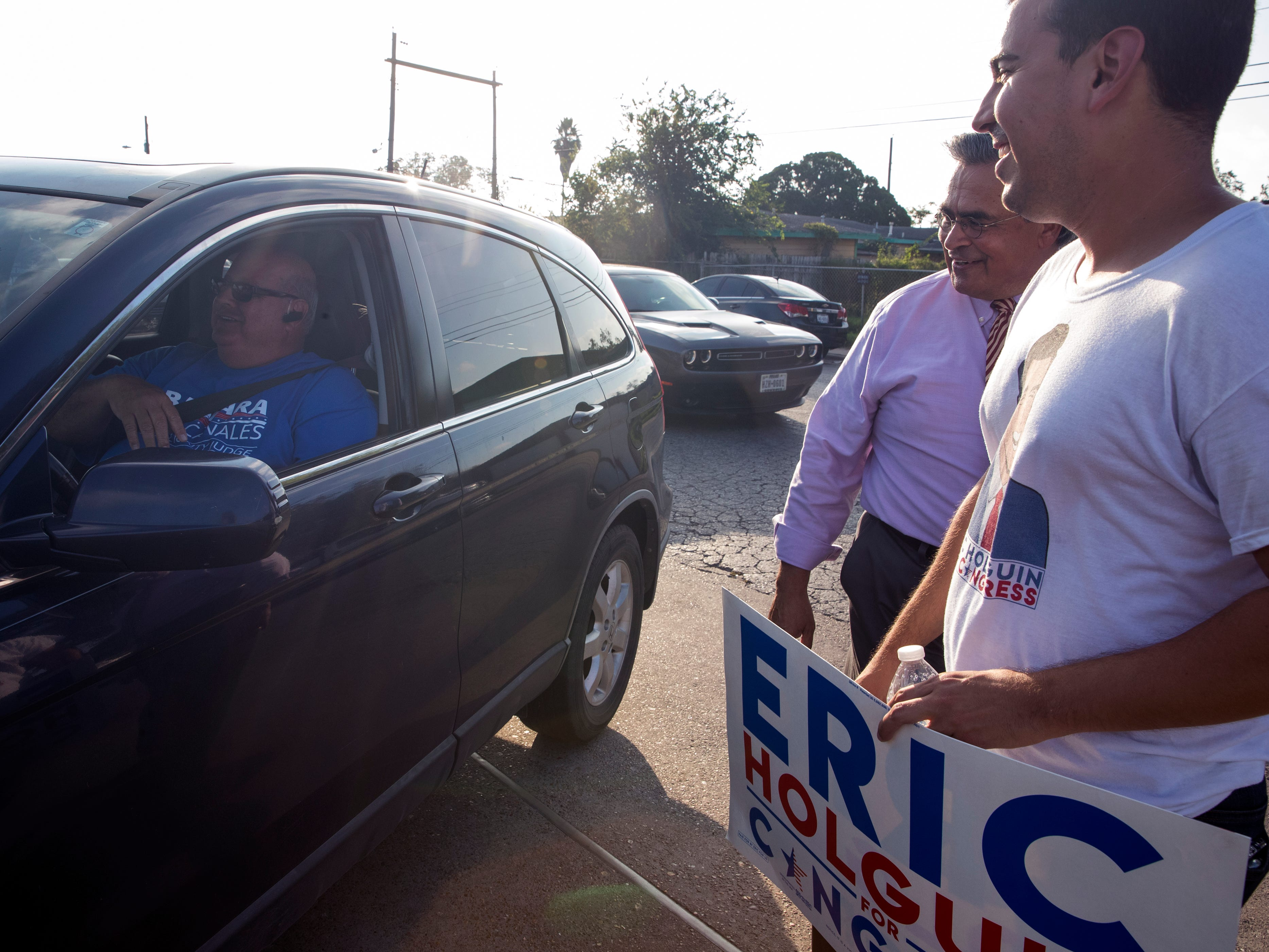 Leo Rio (from left) talks with Carlos Valdez, candidate for 148th District Court Judge, and Eric Holguin, Democratic candidate for Texas' 27th Congressional District, as they campaign outside Moody High School on Tuesday, November 6, 2018.