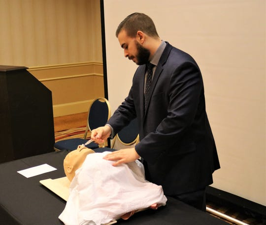 Burlington County Prosecutor's office Detective Steve Laramie demonstrates how to administer naloxone during a seminar with law enforcement and hotel staffers.