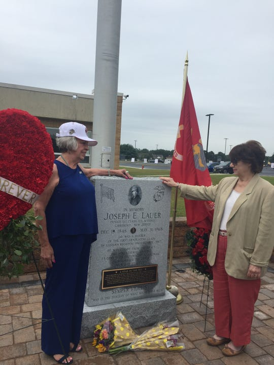 Sue Kent Jones of Virginia, high school sweetheart of Joseph Lauer, admires his newly installed memorial at Eastern Regional  High School with his sister Mary Huber of Berlin Borough, right. Monday the school will dedicate the memorial to U.S. Marine Lauer, a Vietnam War casualty and the only school graduate to die in combat.