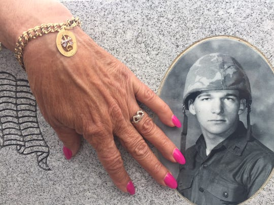 Sue Kent Jones still cherishes the bracelet and ring Vietnam War casualty Joseph Lauer gave her when they were sweethearts at Eastern Regional High School in Voorhees. She touches his  new school memorial at a recent reunion with graduated classmates from 1967 and 1968 who donated money to build the monument, which the school district will dedicate Monday.