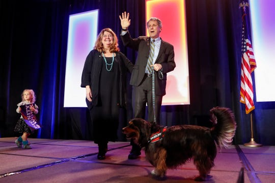 Sen. Sherrod Brown, D-Ohio, right, takes the stage alongside his wife Connie Schultz during the Ohio Democratic Party election night watch party, Tuesday, Nov. 6, 2018, in Columbus, Ohio. (AP Photo/John Minchillo)