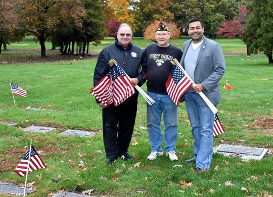 Union County Freeholder Chairman Sergio Granados and Freeholder Angel G. Estrada join Kenilworth VFW 2230 Commander Robert Jeans and dozens of volunteers in placing American flags on veterans' graves in Graceland Cemetery in Kenilworth in honor of Veterans Day on Nov. 3. The Union County Board of Chosen Freeholders supplies more than 30,000 flags to mark veterans' graves throughout Union County.