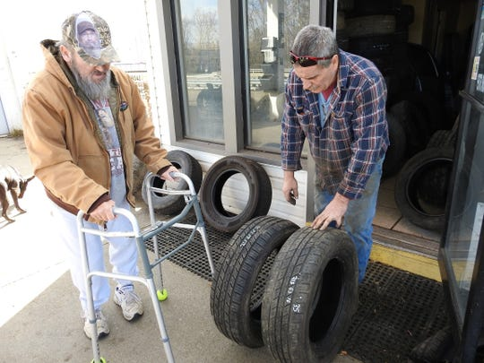 Rodney Hall of Canal Lewisville looks at some tires for his van with Larry Long, owner of the new Warsaw Fix-It Shop.
