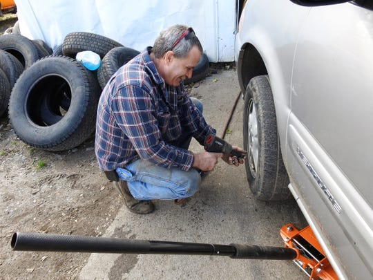 Larry Long loosens lug nuts on a tire at his Warsaw Fix-It Shop, which opened in September.