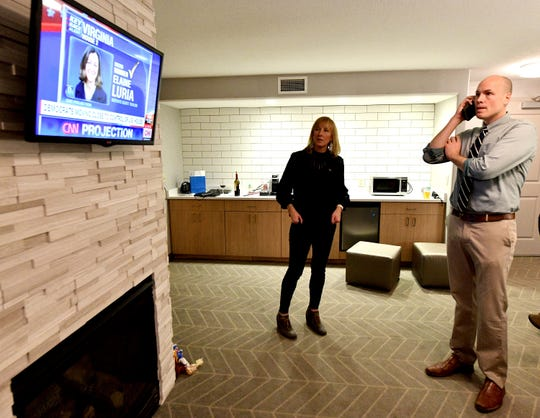 J.D. Scholten, Democratic challenger for Iowa's 4th Congressional District, talks on the phone while watching early election returns with his sister, Jessica Ganley, in a Sioux City hotel room Tuesday evening, Nov. 6, 2018.