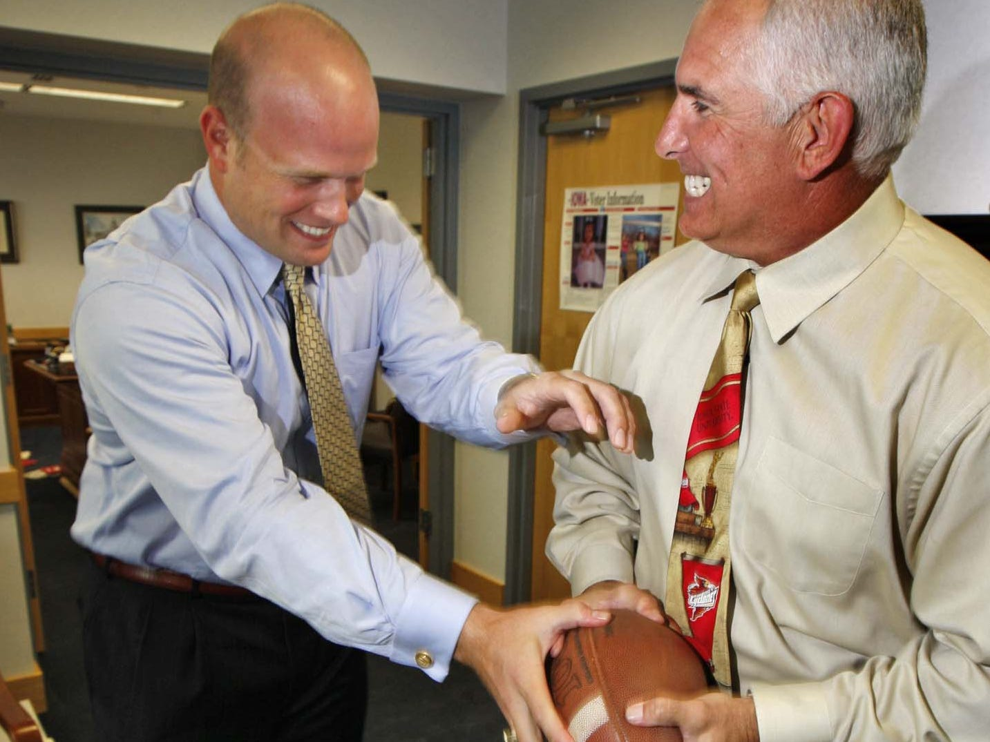 From September 2009: Former Iowa Hawkeyes tight end Matt Whitaker (left), now a U.S. Attorney for the Southern District of Iowa, playfully tries to take the football away from former Iowa State quarterback John Quinn, who is the Director of the division of criminal investigations in Iowa.