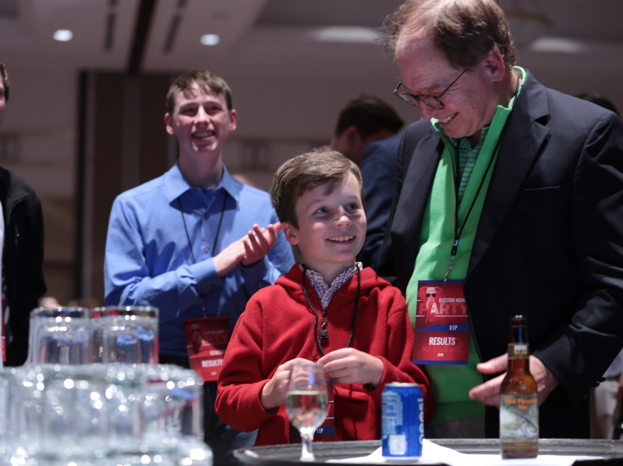 Kurt Holland of Ann Arbor and his son Keating Holland watch results during an Michigan Republican midterm election night party at the Lansing Center in Lansing on Tuesday, November 6, 2018.
