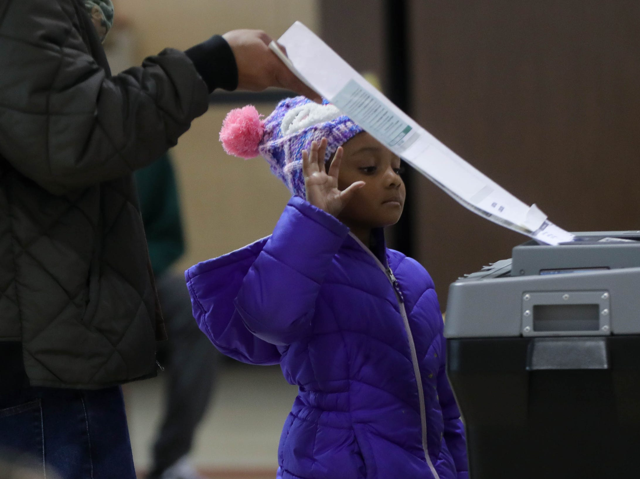 Layla Wilson 6, helps her dad Linwood Wilson cast his vote Tuesday, November 6, 2018 at the 8th precinct in East Pointe, Mich.