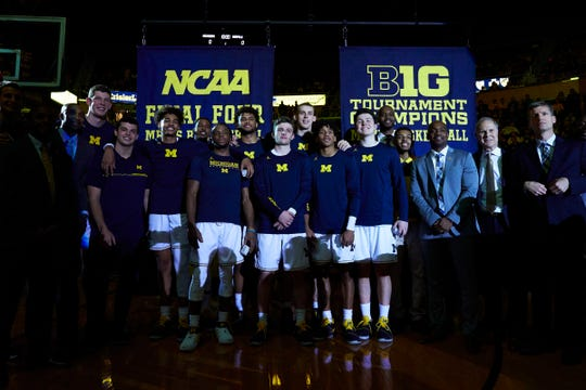 Michigan raise banners for their Final Four appearance and Big Ten Tournament championship prior to the season opener at Crisler Center.