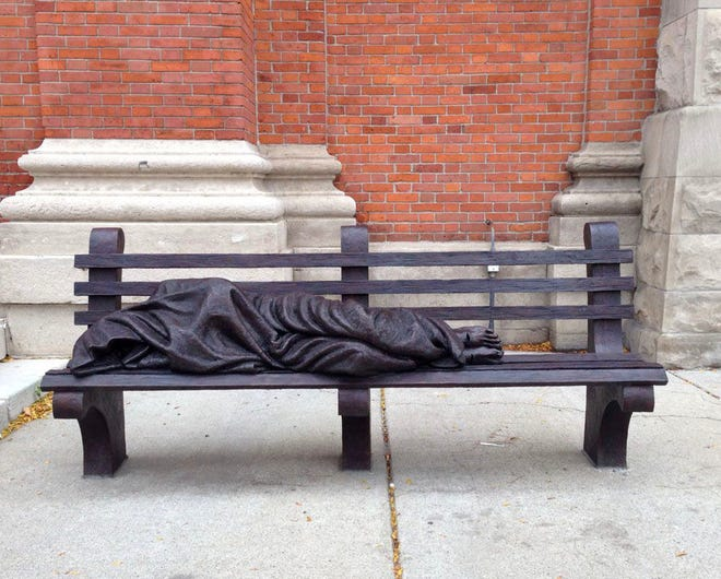 """A """"Homeless Jesus"""" statue is in front of Saints Peter and Paul Jesuit church in downtown Detroit."""