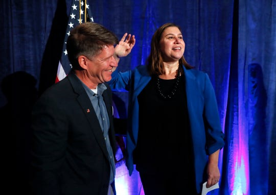 Elissa Slotkin, Democratic candidate for Michigan's 8th Congressional District, waves to supporters with her husband David Moore at an election night watch party in Clarkston, Mich., Wednesday, Nov. 7, 2018. Slotkin is challenging Republican incumbent Mike Bishop. (AP Photo/Paul Sancya)