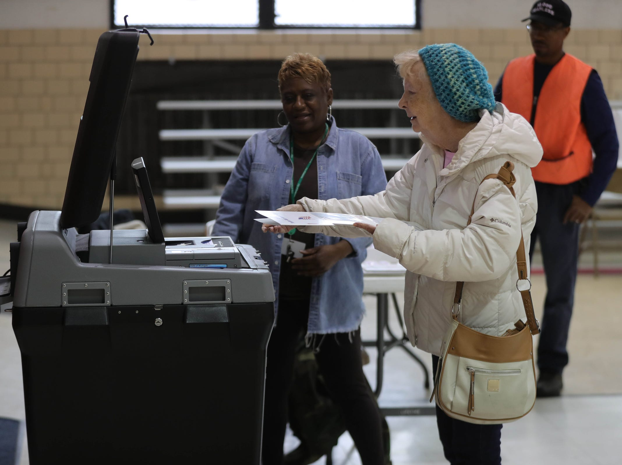 Carol Richardson helps Barbara Van Hooser cast her vote Tuesday, November 6, 2018 at the 7th precinct in East Pointe, Mich.