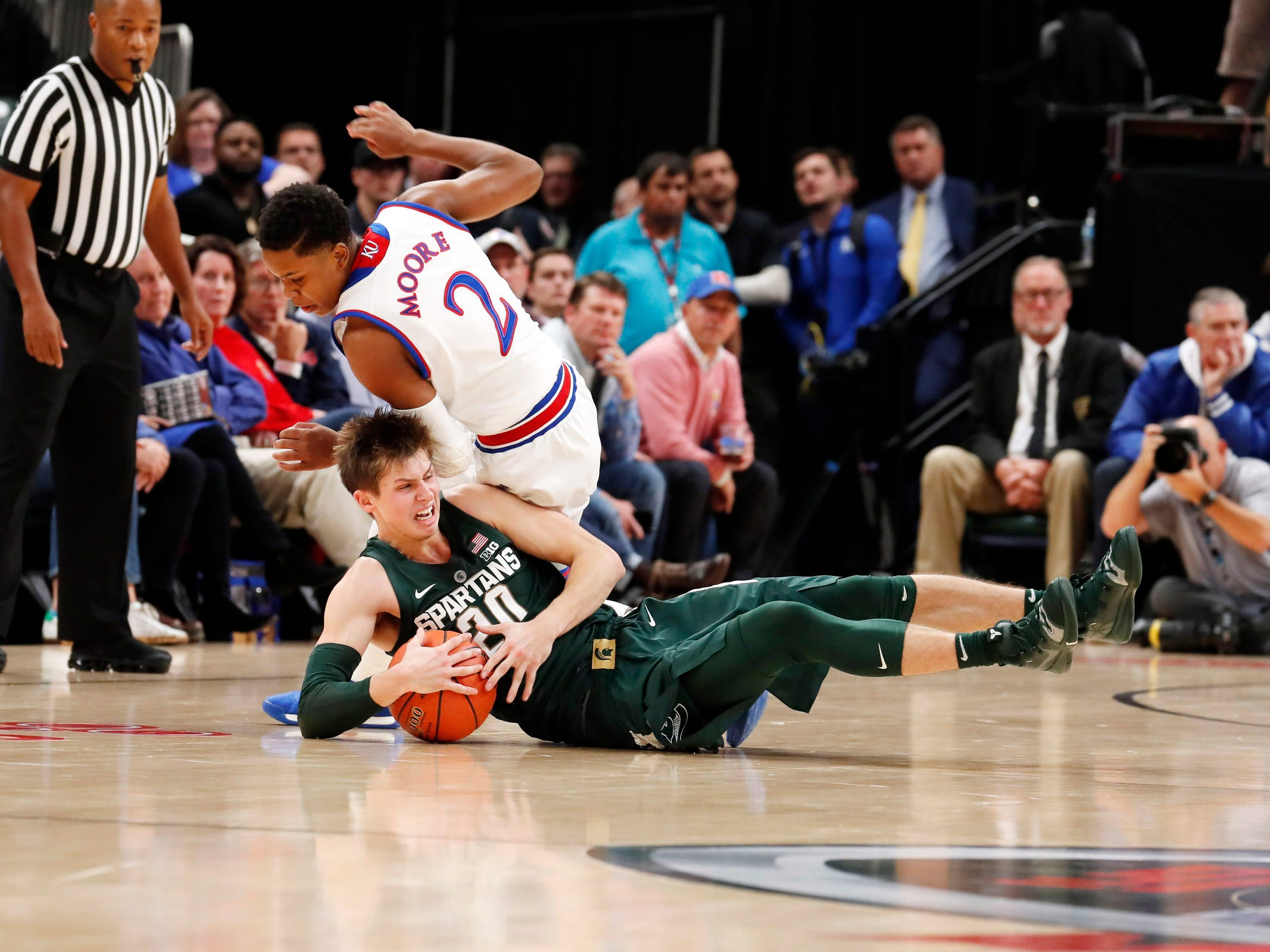 Michigan State guard Matt McQuaid scrambles for a loose ball against Kansas guard Charlie Moore in the first half during the Champions Classic at Bankers Life Fieldhouse, Nov. 6, 2018 in Indianapolis.