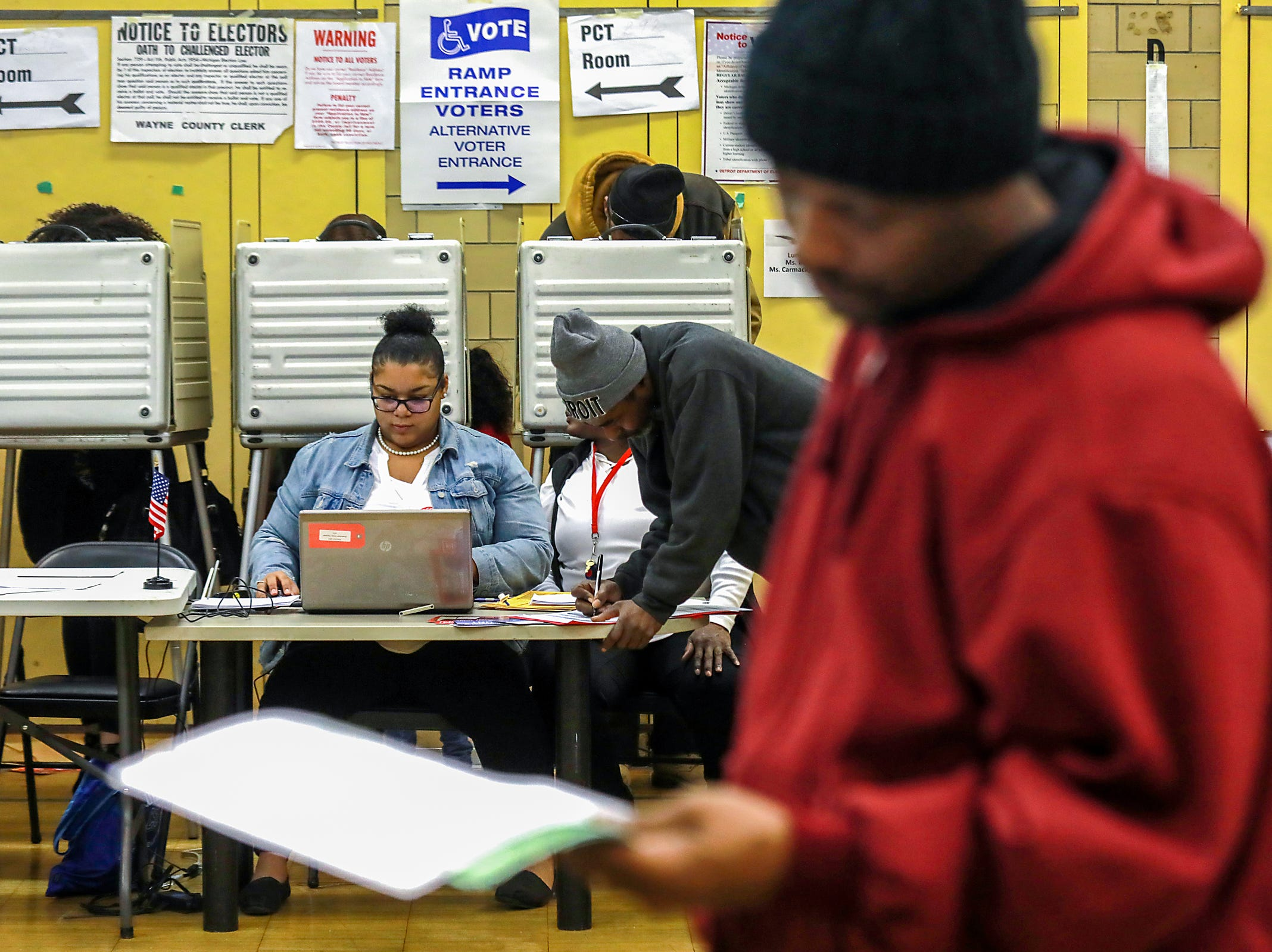 Tiara Taylor, 22, works as an electronic poll worker at Bow elementary-middle school on Michigan midterm elections day in Detroit on Tuesday, Nov. 6, 2018.