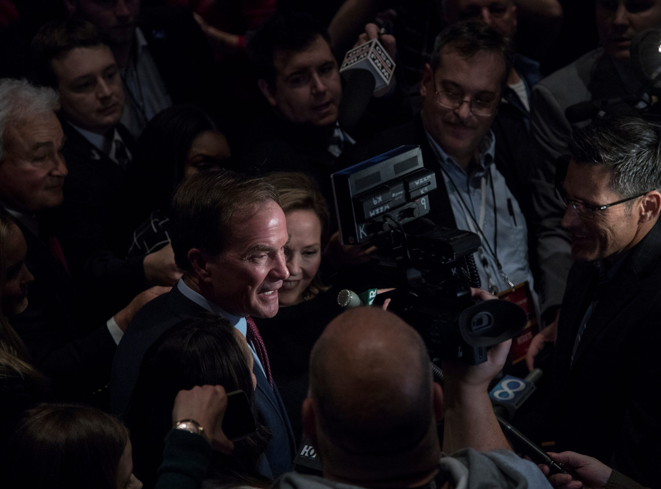 Republican gubernatorial candidate Bill Schuette, center, next to his wife Cynthia Grebe talks to media members after his concession speech at the Lansing Center in Lansing, Tuesday, Nov. 6, 2018.