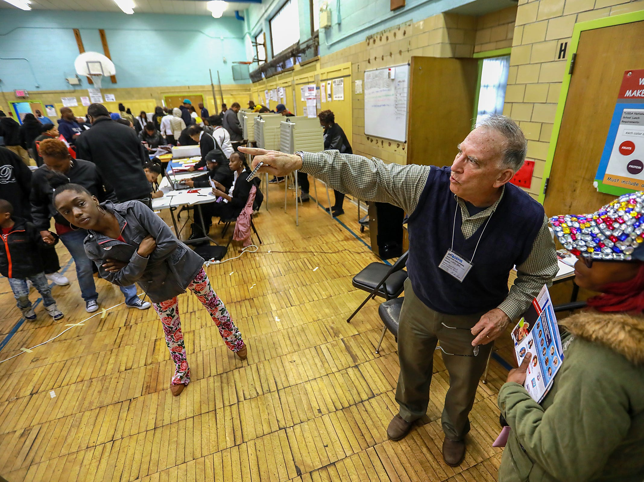 Larry Root, 72, of Ann Arbor is a democratic poll watcher and directs Voters to their precincts to vote at Bow elementary-middle school on Michigan midterm elections day in Detroit on Tuesday, Nov. 6, 2018.