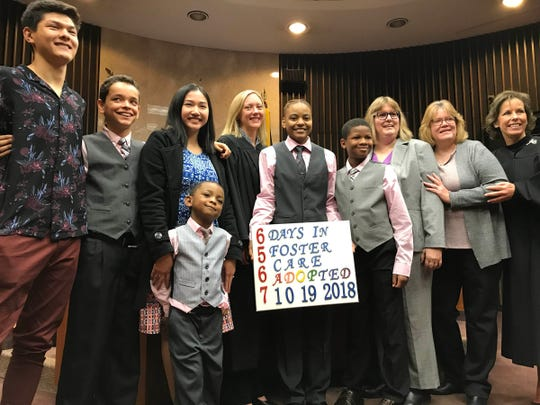 From left to right: Bennett Malburg, 16; Joshua Lange, 11; Alissa Malburg, 19; Caiden Lange, 4; Michigan Supreme Court Justice Elizabeth Clement; C'Nai Lange, 17; Deante Lange, 10; Lisa Lange; Kathy Lange, and Macomb County Circuit Court Judge Tracey Yokich in Macomb County Circuit Court on Oct. 19, 2018.