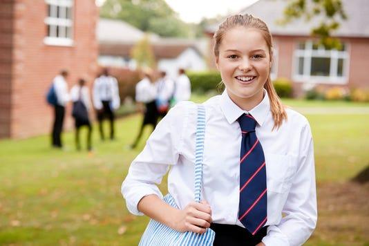 Portrait Of Female Teenage Student In Uniform Outside Buildings