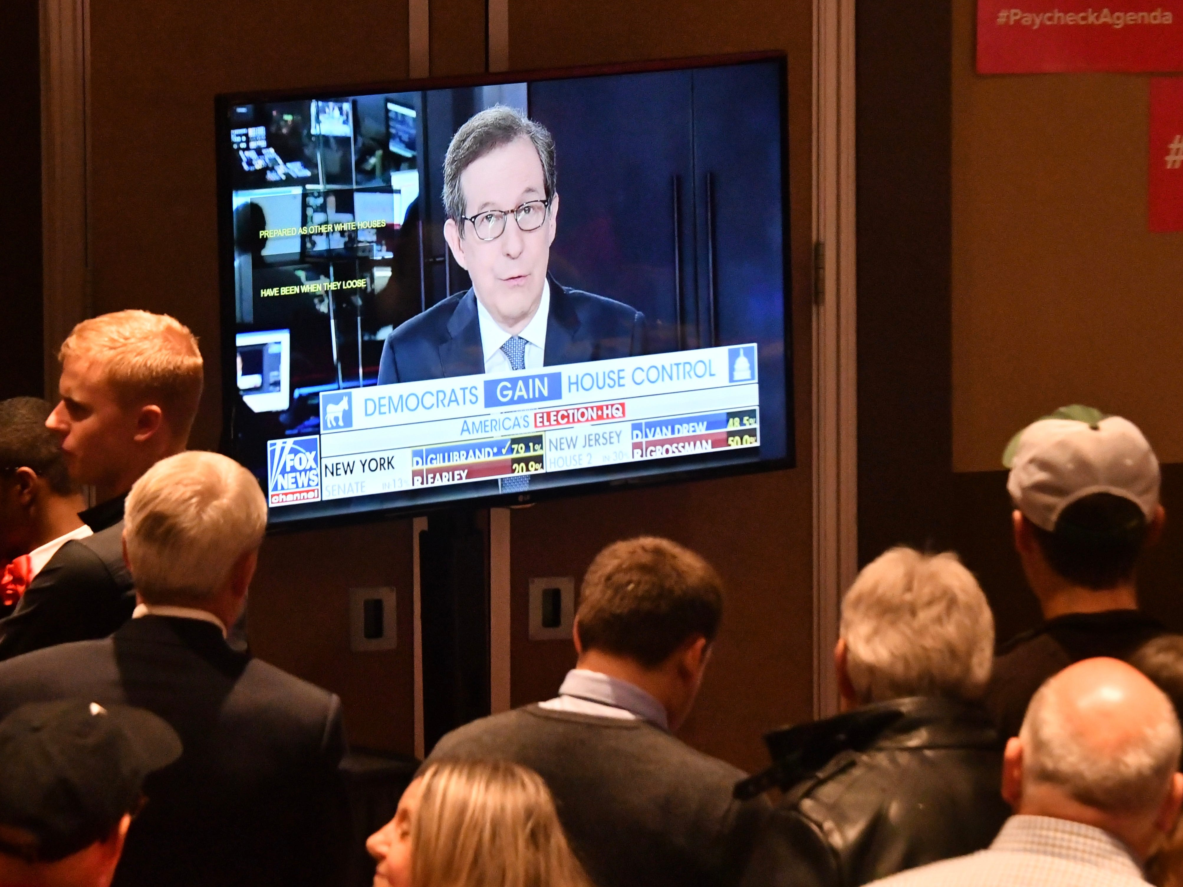 People gather around the television at the Republican election night party at the Lansing Center.
