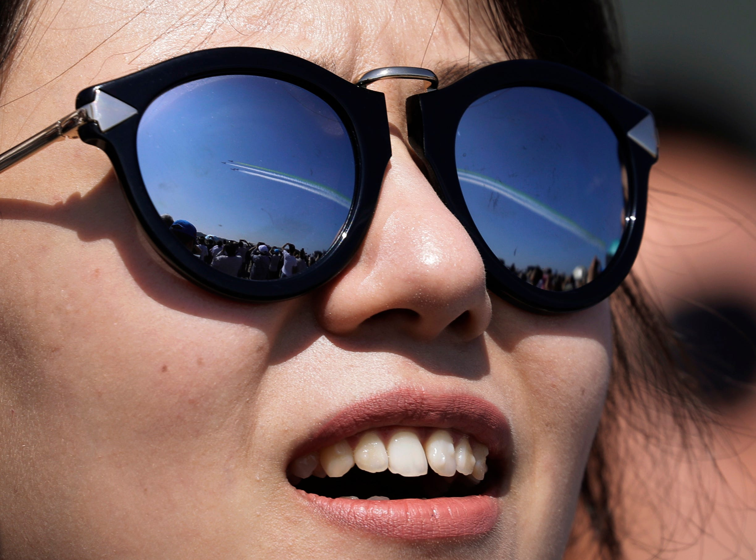 A spectator's sunglasses reflect China's K-8 aircrafts performing at the 12th China International Aviation and Aerospace Exhibition in Zhuhai city, south China's Guangdong province, Wednesday, Nov. 7, 2018.