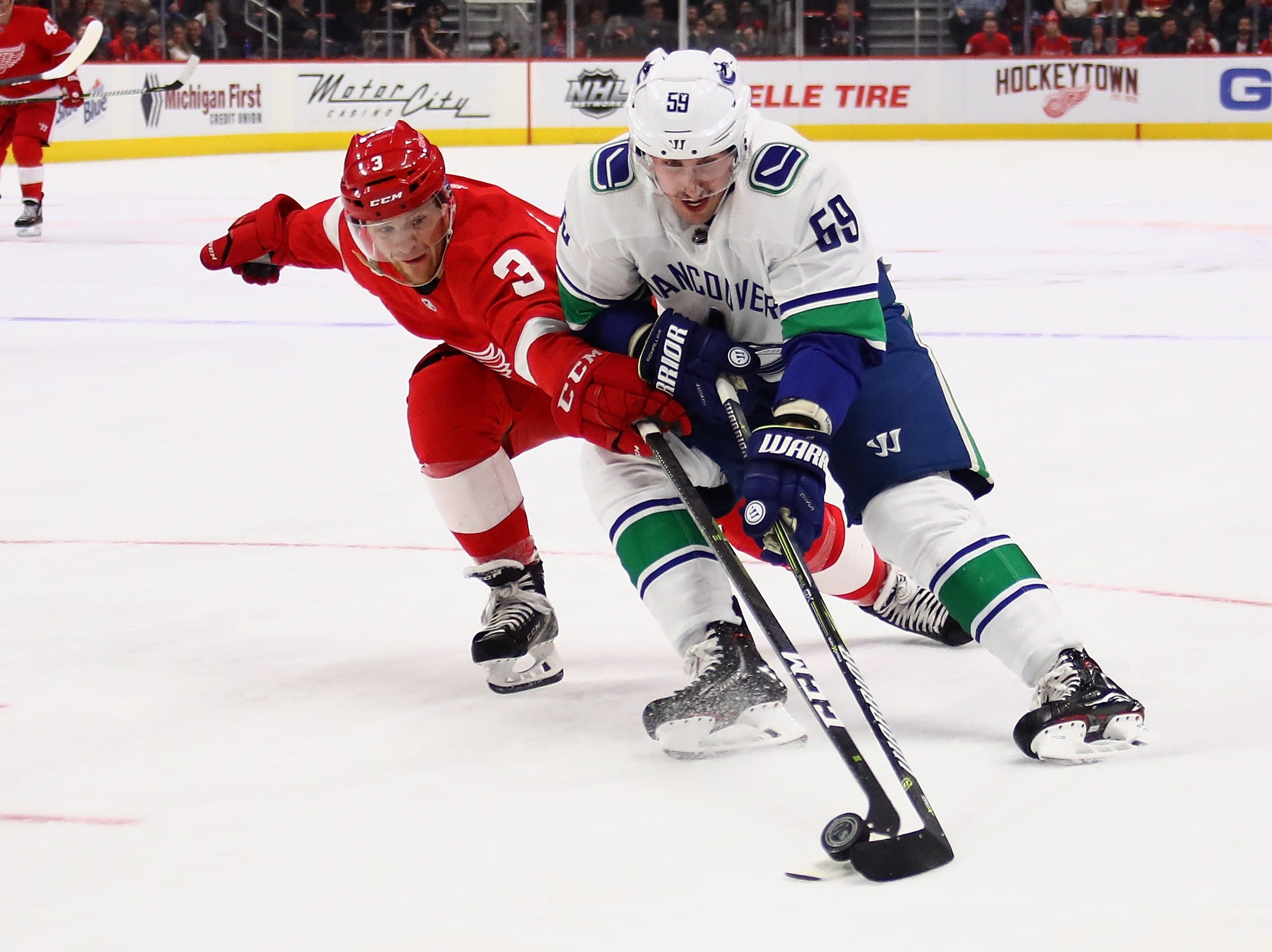 Tim Schaller (59) of the Vancouver Canucks tries to get around the stick of Nick Jensen (3) of the Detroit Red Wings during the first period at Little Caesars Arena on November 06, 2018 in Detroit, Michigan.